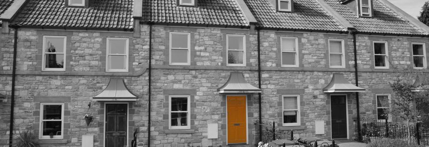 A row of 5 houses, possibily new builds, in black and white, with one of the front doors highlighted in orange which is the colour for Grange Mortgage